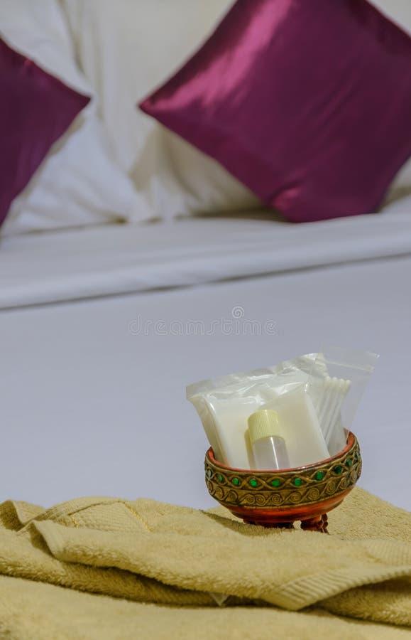 Insieme della doccia ed asciugamano giallo sul letto bianco fotografia stock