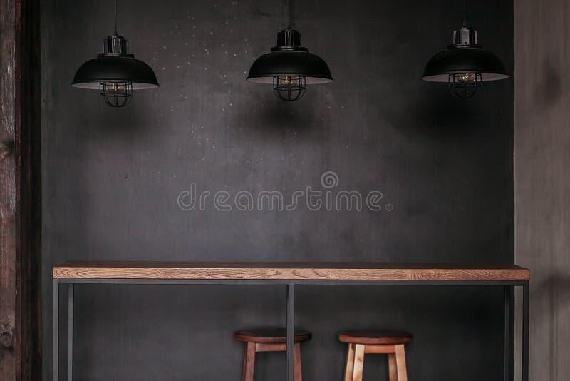 Insieme della tavola di Dinning nella sala da pranzo di stile del sottotetto con le lampade nere fotografia stock
