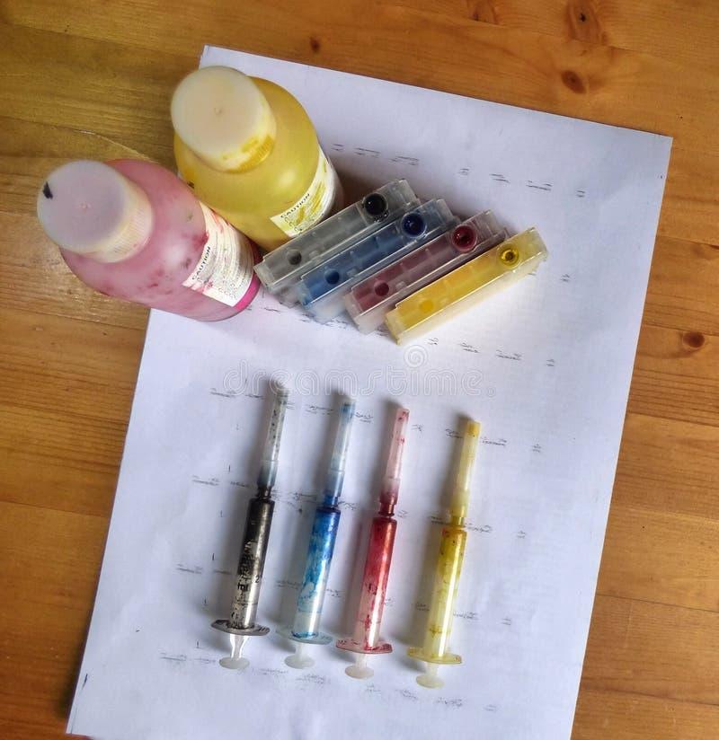 Insieme delle cartucce di inchiostro, delle pitture della ricarica in bottiglie e di syring sporco fotografia stock libera da diritti