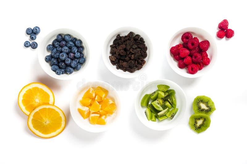 Insieme delle ciotole bianche in pieno di frutta fresca secca e sistemata come cinque anelli olimpici immagine stock libera da diritti