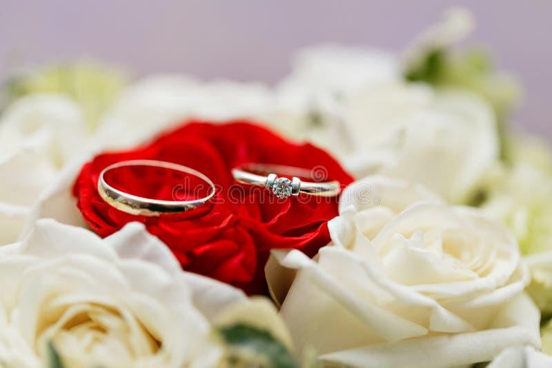 Insieme delle fedi nuziali e bianca primo piano preso in rosa rossa Arco della stella blu con il nastro blu (involucro di regalo) immagine stock