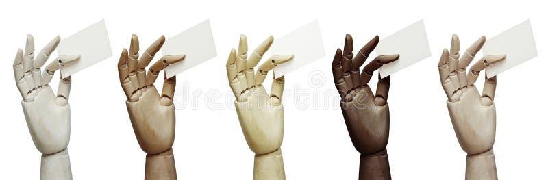 Insieme delle mani di legno dei colori differenti che tengono i biglietti da visita immagini stock