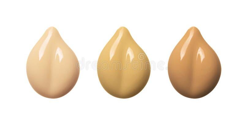 Insieme delle sbavature del fondamento di trucco isolato su fondo bianco Campione cosmetico beige della crema di BB Polvere liqui immagine stock