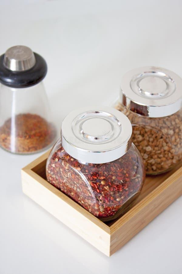 Insieme delle spezie in barattoli di vetro cottura Ingredienti di alimento Papper e radice del prezzemolo immagini stock