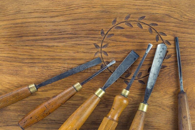 Insieme dello scalpello da legno per la scultura del legno, strumenti della scultura su fondo di legno fotografia stock libera da diritti