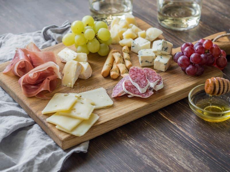 Insieme dello spuntino del vino della carne e del formaggio sul bordo di legno Varietà di formaggio, di salame, di prosciutto di  fotografie stock libere da diritti