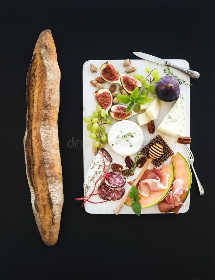Insieme dello spuntino e del vino Baguette, fichi, uva, dadi, varietà del formaggio, aperitivi della carne, erbe sul bordo di leg immagini stock