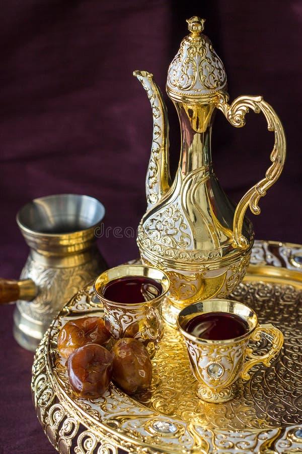 Insieme di caffè arabo dorato tradizionale con dallah, la caffettiera e le date Fondo scuro immagine stock
