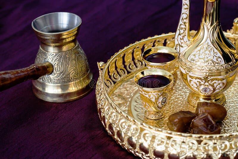Insieme di caffè arabo tradizionale dorato con dallah, il jezva della caffettiera, la tazza e le date Fondo scuro fotografie stock