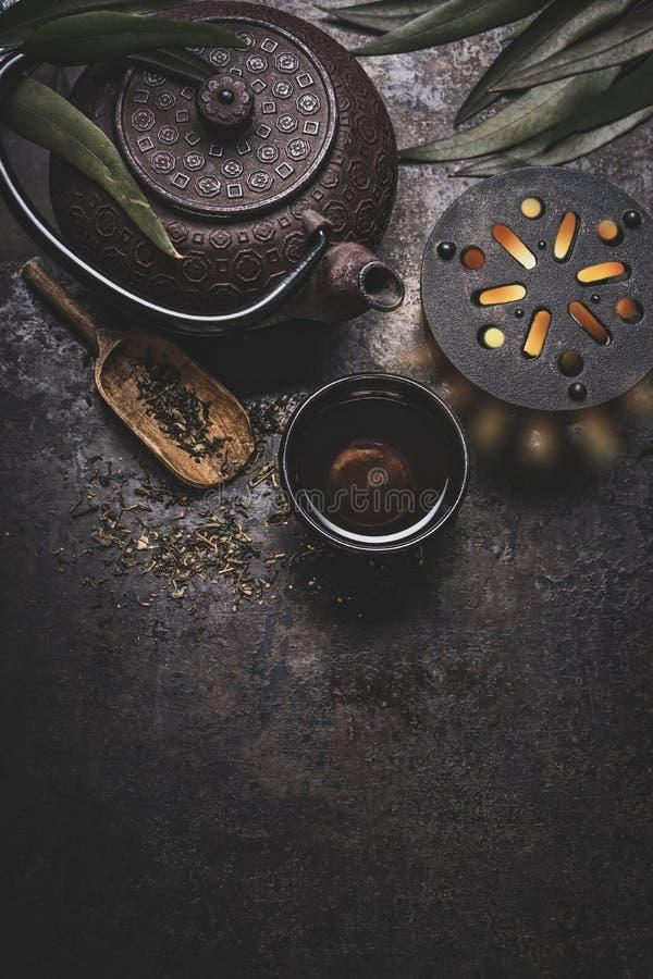 Insieme di tè asiatico del ferro nero su fondo rustico scuro con la teiera e le foglie di tè fresche, vista superiore fotografie stock