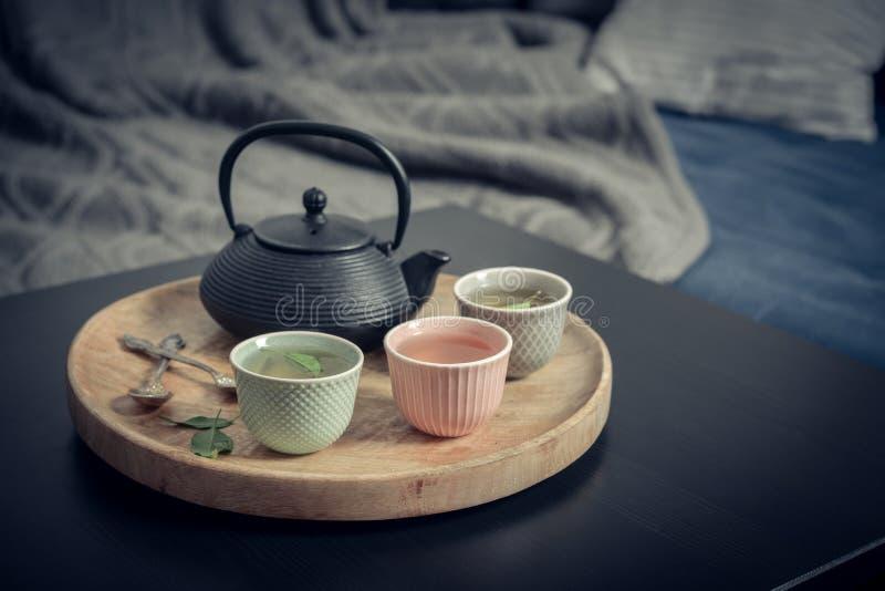 Insieme di tè asiatico del ferro nero sul vassoio di legno fotografie stock