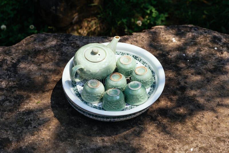 Insieme di tè ceramico verde chiaro compreso il barattolo, le tazze ed il piatto sulla tavola di pietra sotto l'ombra dell'albero fotografie stock libere da diritti