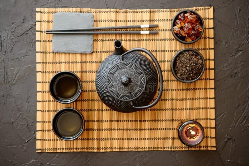Insieme di tè verde asiatico sulla stuoia di bambù fotografia stock