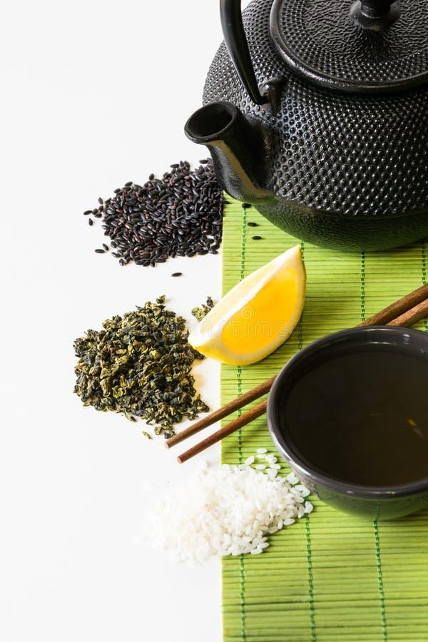 Insieme di tè verde asiatico sulla stuoia di bambù con tè verde secco, limone, riso in bianco e nero Concetto asiatico del tè fotografia stock