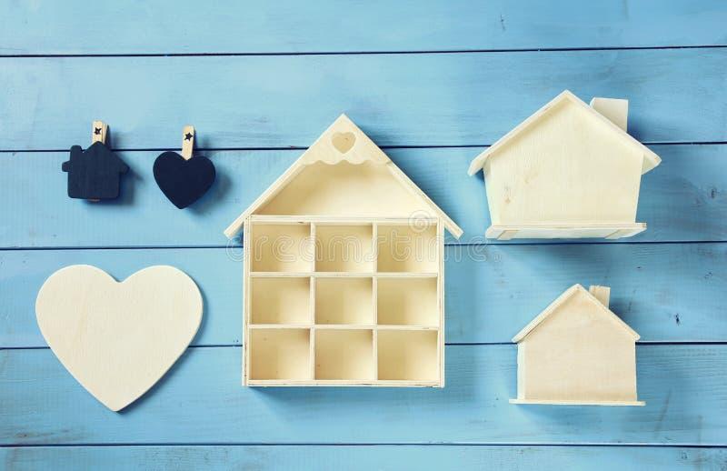 Insieme di varie case di legno su fondo di legno blu, immagine di vista superiore immagine stock libera da diritti