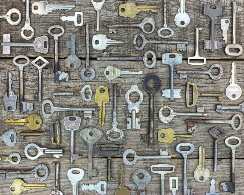Insieme di vecchie chiavi arrugginite sui bordi rustici di legno grigi fotografia stock