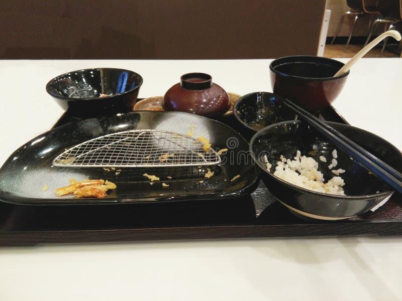 Insieme giapponese vuoto dell'alimento della tempura, rimasto i residui della tempura sul piatto e su un certo riso in ciotola, fotografie stock libere da diritti