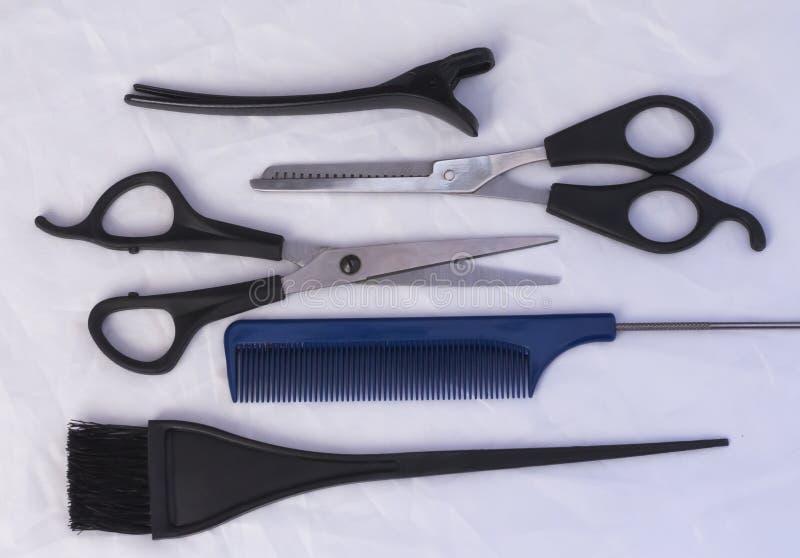 Insieme professionale di lavoro di parrucchiere sulla tavola bianca, composizione piana immagine stock