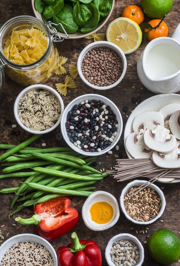 Insieme vegetariano dell'alimento dei prodotti - cereali, verdure, frutta, pasta, semi su un fondo di legno marrone, vista superi fotografia stock libera da diritti
