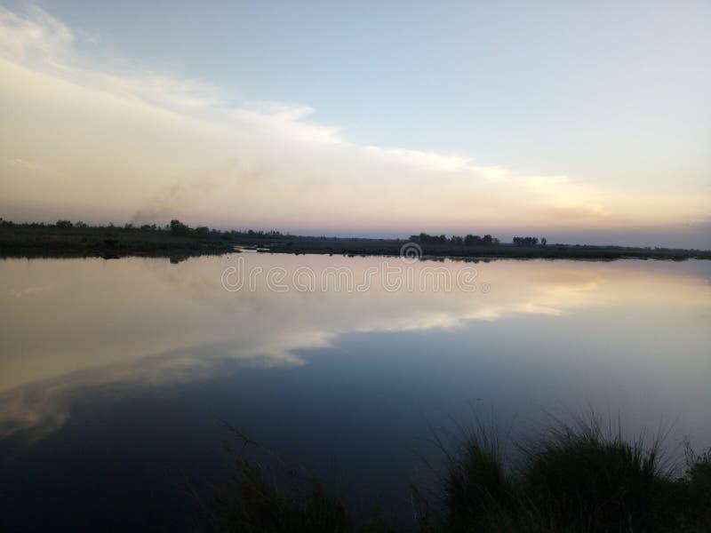 Insiemi di Sun al fiume immagini stock libere da diritti