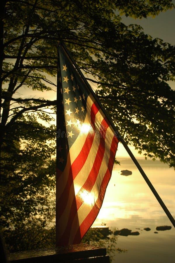 Insiemi di Sun dietro la bandiera americana fotografia stock