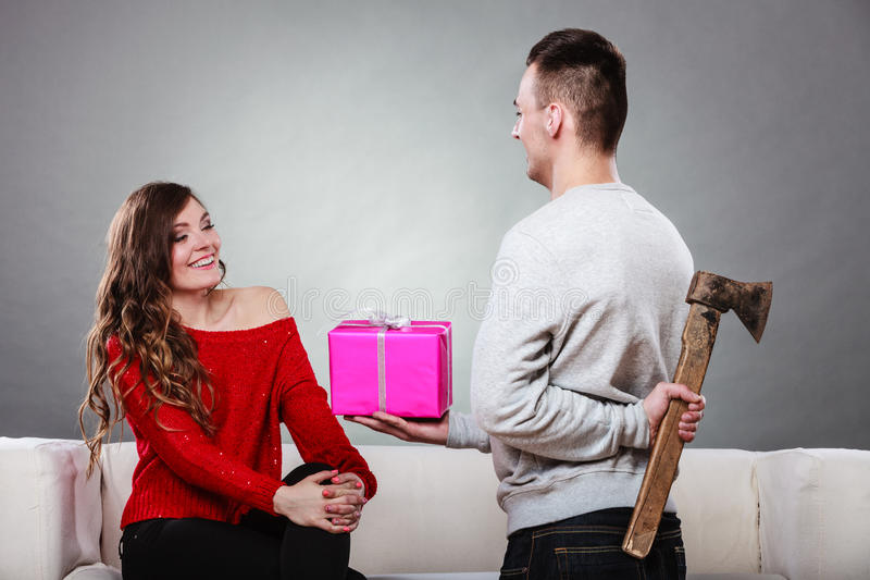 Insincire man holding axe giving gift box to woman. Sneaky insincere men holding axe giving gift present box to woman. Husband concealing hiding his true royalty free stock images