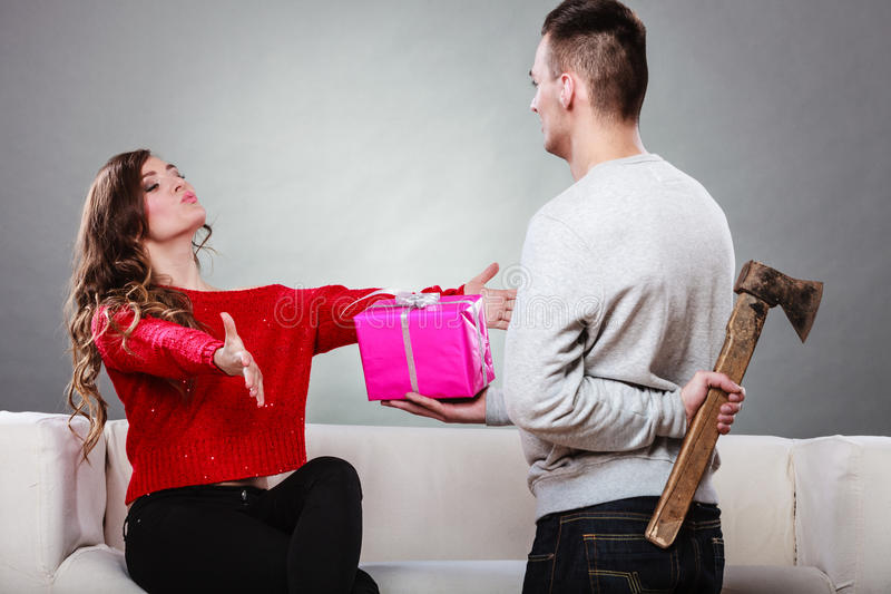 Insincire man holding axe giving gift box to woman. Sneaky insincere men holding axe giving gift present box to woman. Husband concealing hiding his true stock photos