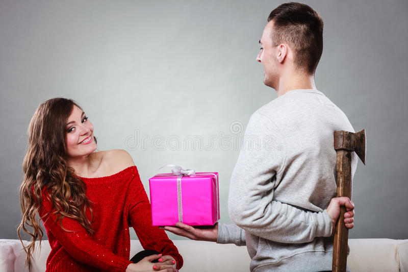 Insincire man holding axe giving gift box to woman. Sneaky insincere men holding axe giving gift present box to woman. Husband concealing hiding his true royalty free stock photography