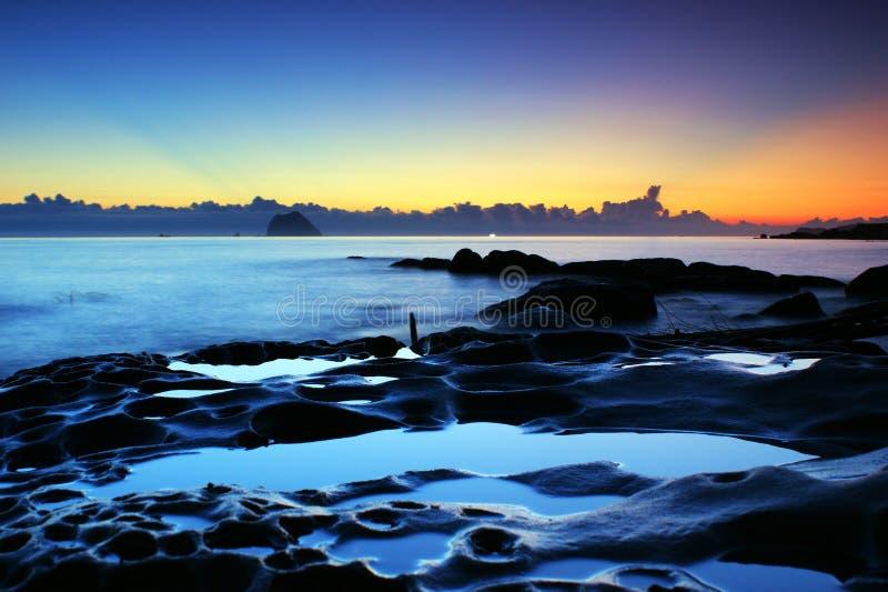 Insinuação do nascer do sol na costa no tom azul fotos de stock royalty free