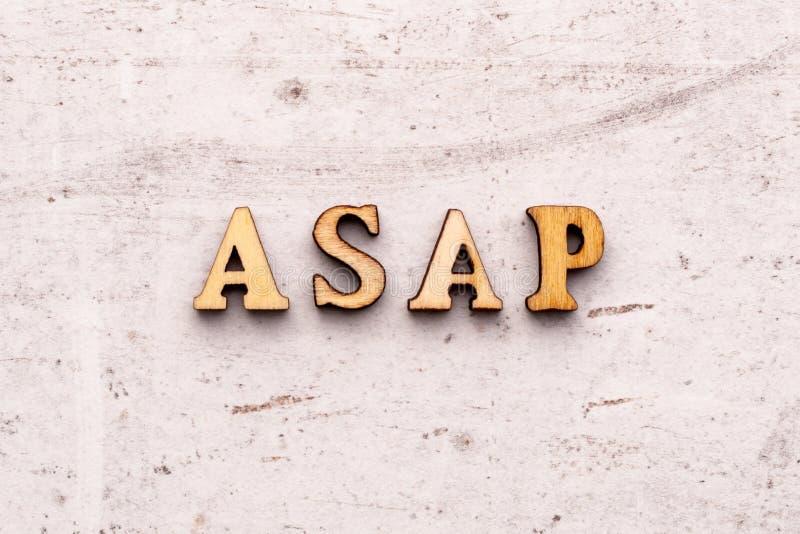 Inskrift ASAP så snart som posisioble förkortning i träbokstäver på en ljus bakgrund arkivfoton