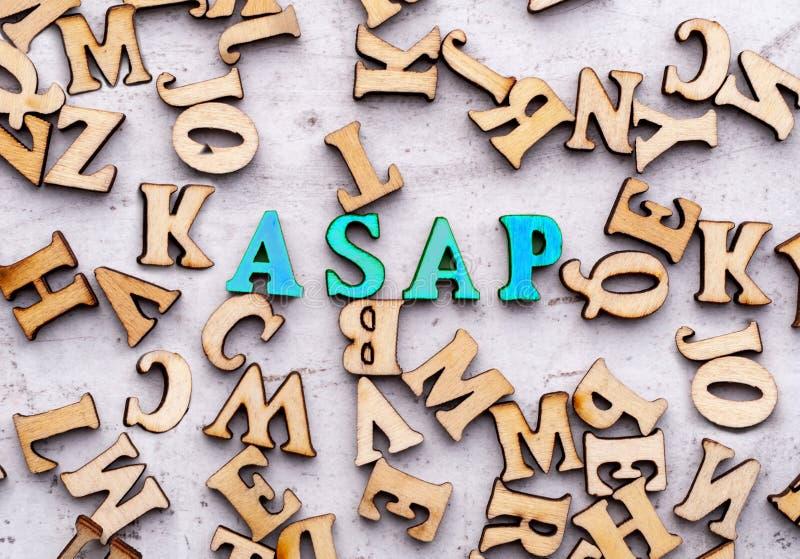 Inskrift ASAP så snart som posisioble förkortning i träbokstäver på en ljus bakgrund royaltyfri fotografi