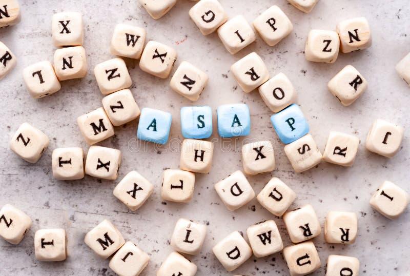 Inskrift ASAP så snart som posisioble förkortning i träbokstäver på en ljus bakgrund royaltyfri bild