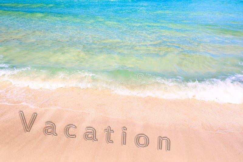 Inskrift av ett semesterord på sanden på den härliga stranden med en blå turkoshavsvåg Begrepp av en sommarsemester och royaltyfria foton
