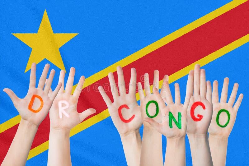 Inskrift DR Congo på barnens händer mot bakgrunden av en vinkande flagga av DREN Congo royaltyfri bild