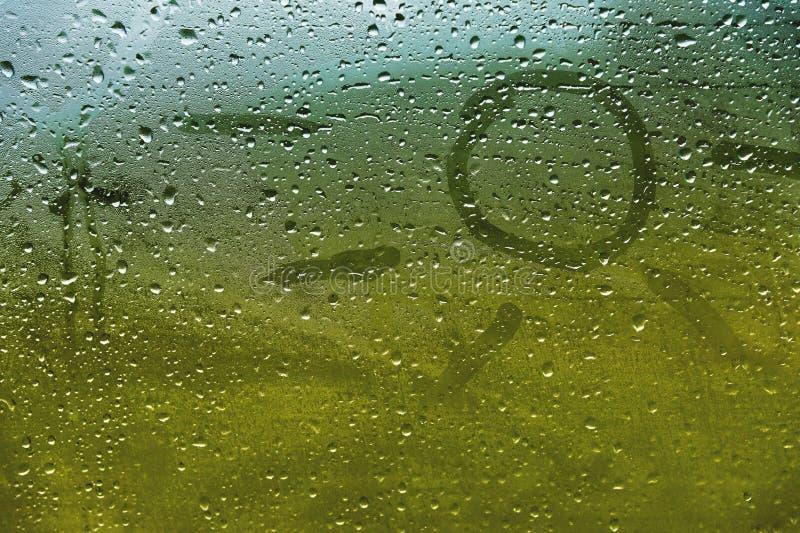 Inskrift för närbildsommarregn på svettigt exponeringsglas Sol och sommarsymbol på grön suddig bakgrund arkivbild