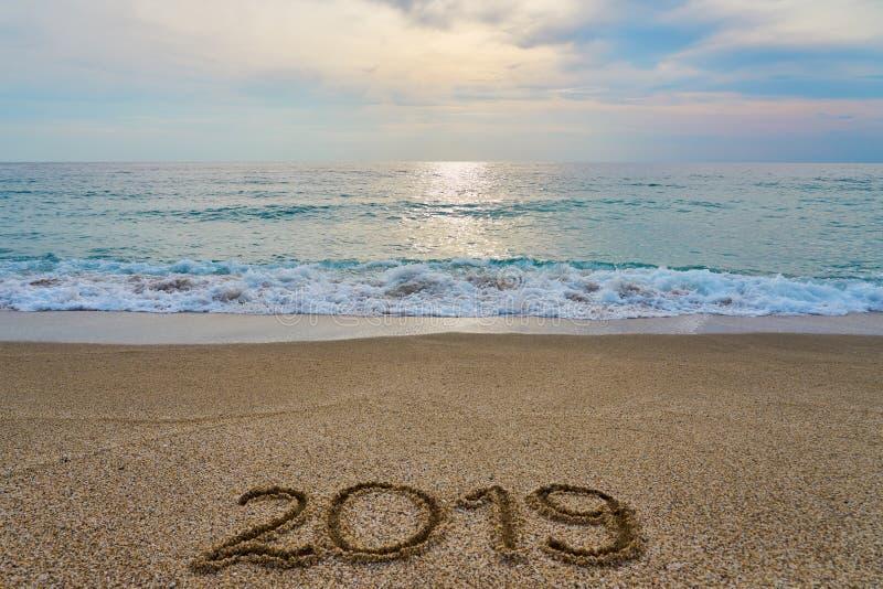 Inskrift 2019 för nytt år som är skriftlig på sanden med det vinkande havet på en solnedgång royaltyfri foto