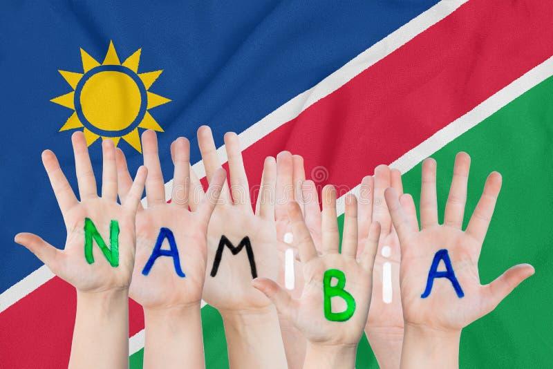 Inskrift Namibia på barnens händer mot bakgrunden av en vinkande flagga av Namibiaet royaltyfria foton