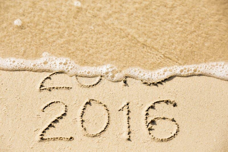 2015 2016 inskrift som är skriftlig i våta gula strandsanden som den är arkivfoton