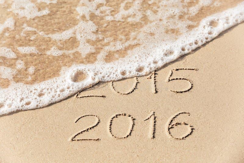 2015 2016 inskrift som är skriftlig i våta gula strandsanden som den är royaltyfria bilder