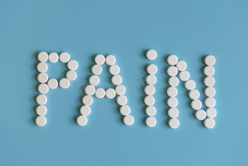 Inskriften av smärtar läggas ut med vita preventivpillerar på en blå bakgrund Smärta kontroll - minnestavlor arkivfoto