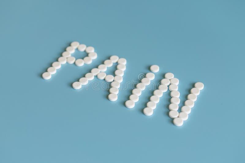 Inskriften av smärtar läggas ut med vita preventivpillerar på en blå bakgrund Smärta kontroll - minnestavlor royaltyfria foton