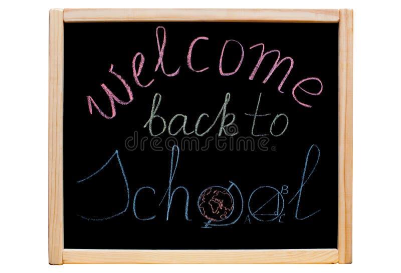 Inskriften & x22en; välkomnande tillbaka till school& x22; skriftligt med färgrik krita på en skola, svart bräde arkivbild