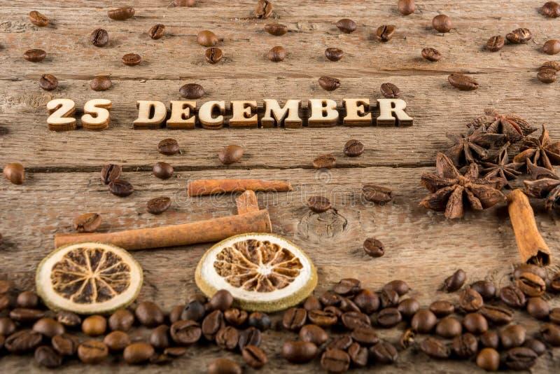 Inskriften från träbokstäver och nummer 'December 25', en cykel och ett träd från kryddor på bakgrunden av grovt trä royaltyfri bild