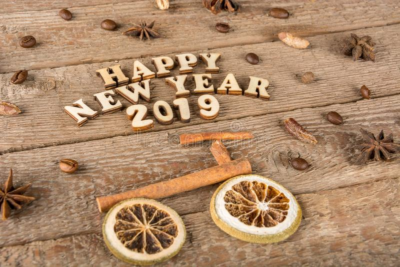 Inskriften från träbokstäver och nummer 'lyckligt nytt år ', en cykel och ett träd från kryddor på bakgrunden av grovt trä royaltyfria foton