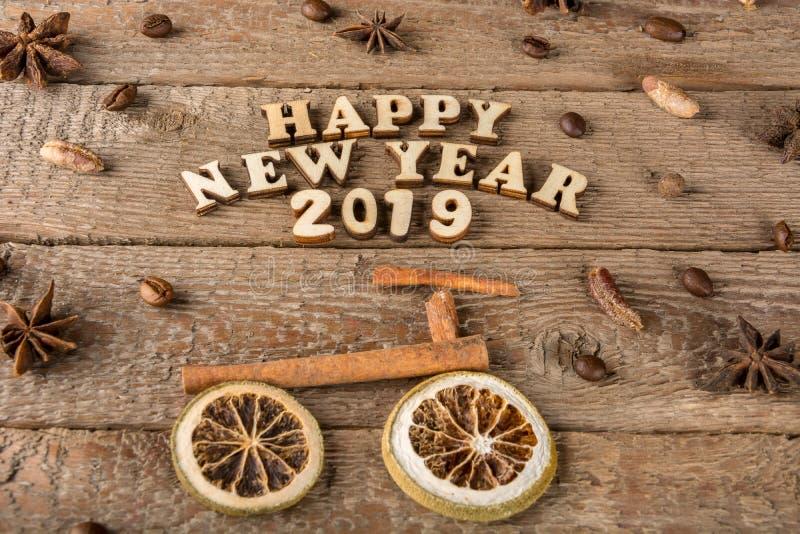 Inskriften från träbokstäver och nummer 'lyckligt nytt år ', en cykel och ett träd från kryddor på bakgrunden av grovt trä arkivbilder