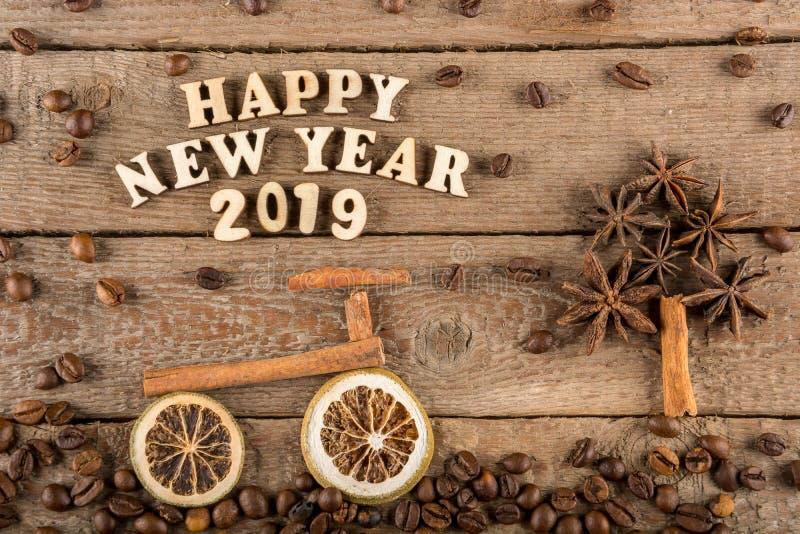 Inskriften från träbokstäver och nummer 'lyckligt nytt år ', en cykel och ett träd från kryddor på bakgrunden av grovt trä arkivfoton