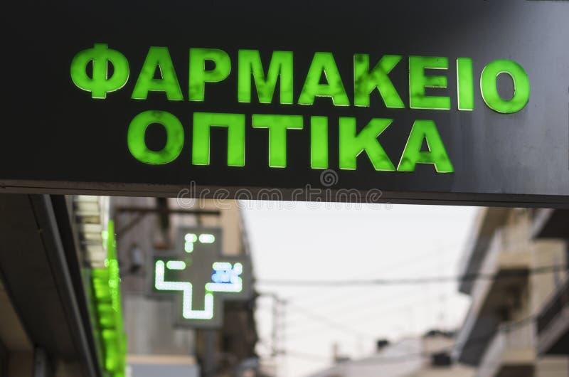 Inskriften i grekiskt 'apotek 'och att glöda korsar royaltyfri foto