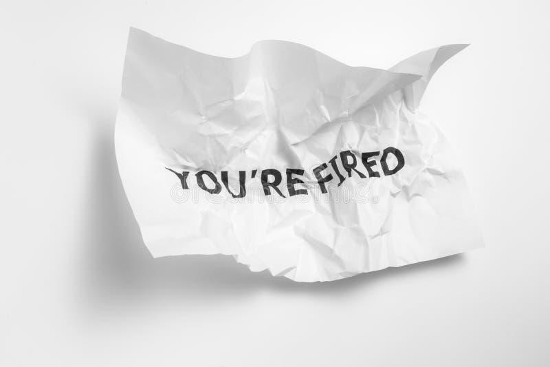 Inskriften på den skrynkliga pappers- `en är du avfyrad ` som ett meddelande från arbetsplatsen royaltyfria bilder