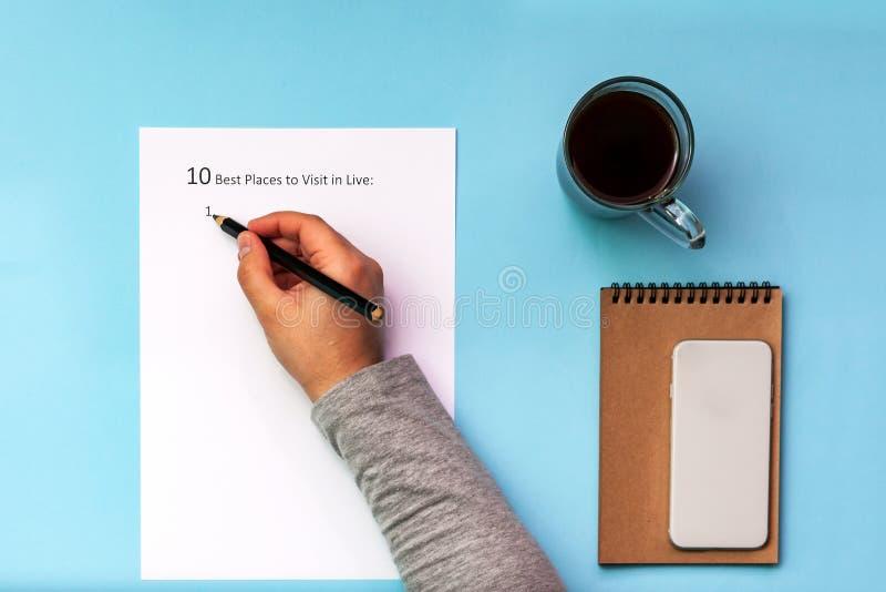 Inskriften på ett vitt ark av bästa plases A4 10 som ska besökas i levande På en blå bakgrund med en kopp kaffe och en anteckning arkivbilder