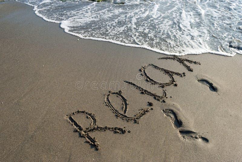 Inskriften på sanden, kopplar av, sätter på land, semestrar royaltyfri fotografi